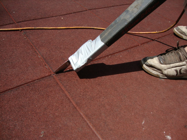Close up image of cleaning the seams with a putty-knife taped to the end of a blower